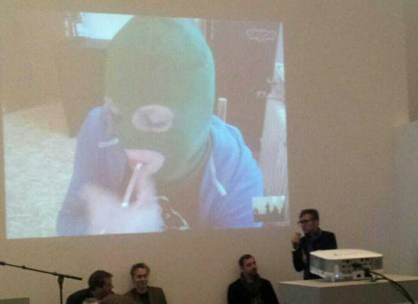 Eine Frau mit grüner Sturmhaube zündet sich eine Zigarette an, sie wird via Beamer auf das Podium einer Diskussion mit vier Männern zugeschaltet.